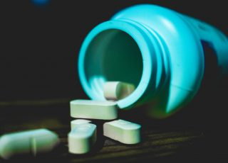 Photo of a pill bottles tipped over and white pills on a table. Photo by Jonathan Perez on Unsplash.