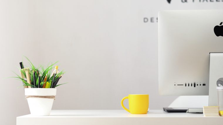A desk with a small plant in a pot, a yellow mug and a mac computer