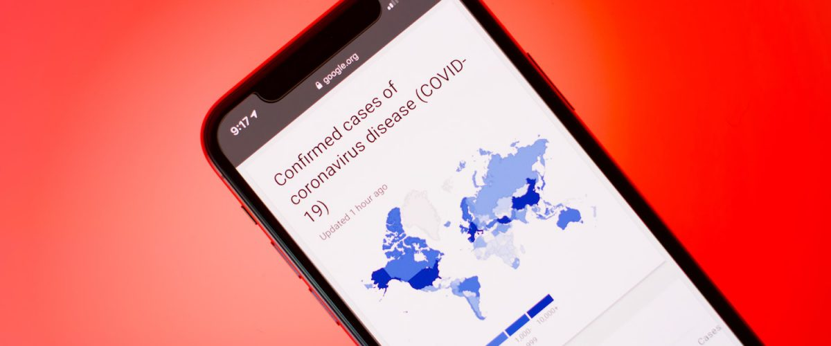 Smartphone with a map showing the spread of COVID-19 virus worldwide.